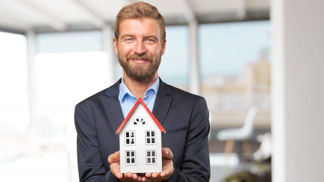 Hymyilevä mies pitää pienoismalli-taloa käsissään ja ojentaa sitä kuvaajaa kohti. Optima osallistuu Isännöinti-päiville 6.-8.9.2017.