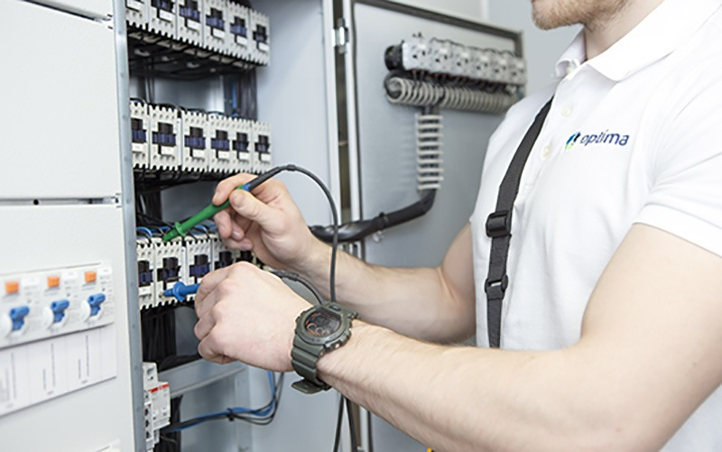Optima Talotekniikan sähkömies tekemässä sähköpääkeskuksen ääressä säätöjä