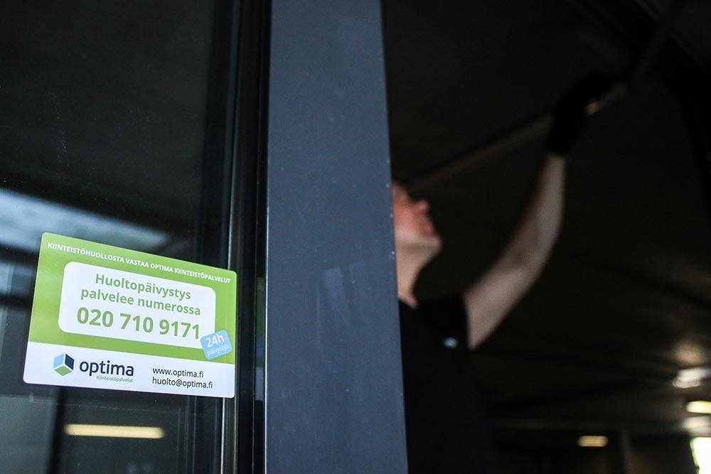 Optima Kiinteistöpalveluiden tarra  huoltosopimus-kohteen ovenpielessä. Taustalla huoltomies korjaa ovea.