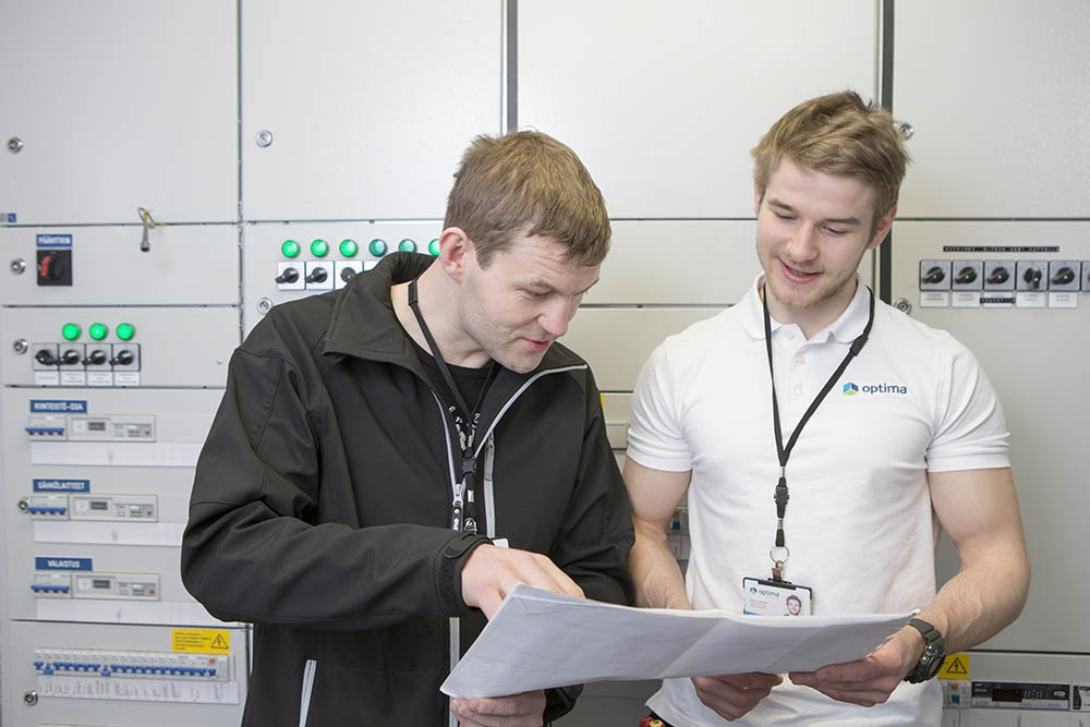 Sähkötyöt sisältää paljon suunnittelua - Optima Talotekniikan kaksi sähkömiestä tutkii papereita sähköpääkeskuksessa.