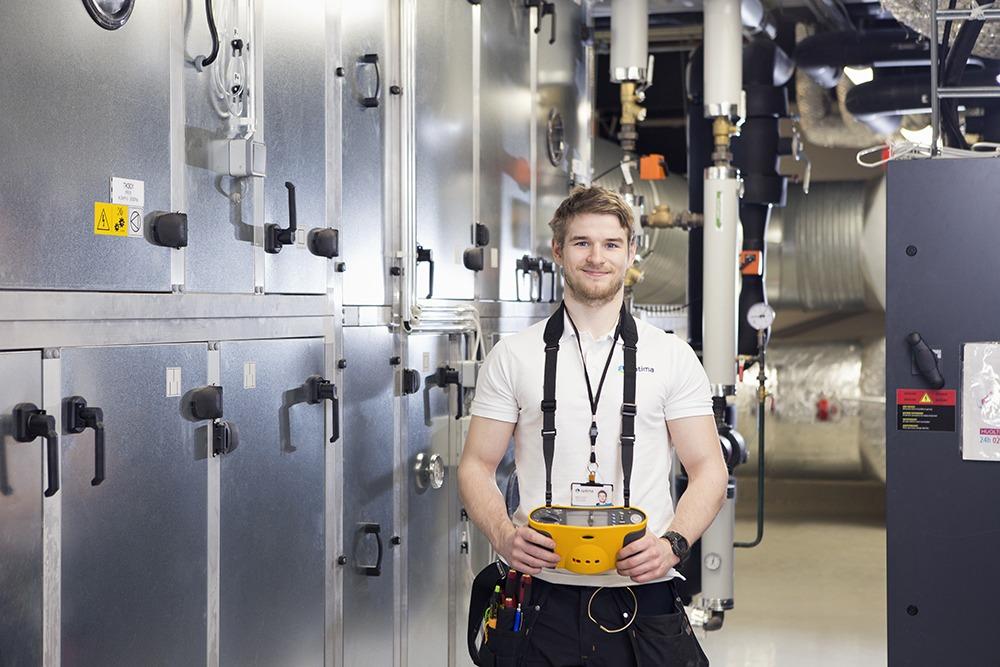 Talotekniikka-asiantuntija seisoo huoltokoneiden keskellä ja pitelee käsissään säätölaitetta