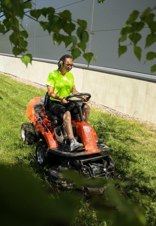 Kiinteistönhoitaja ajaa ruohonleikkuria kuulokkeet korvillaan ja huolehtii kiinteistön ulkotyöt kuntoon.