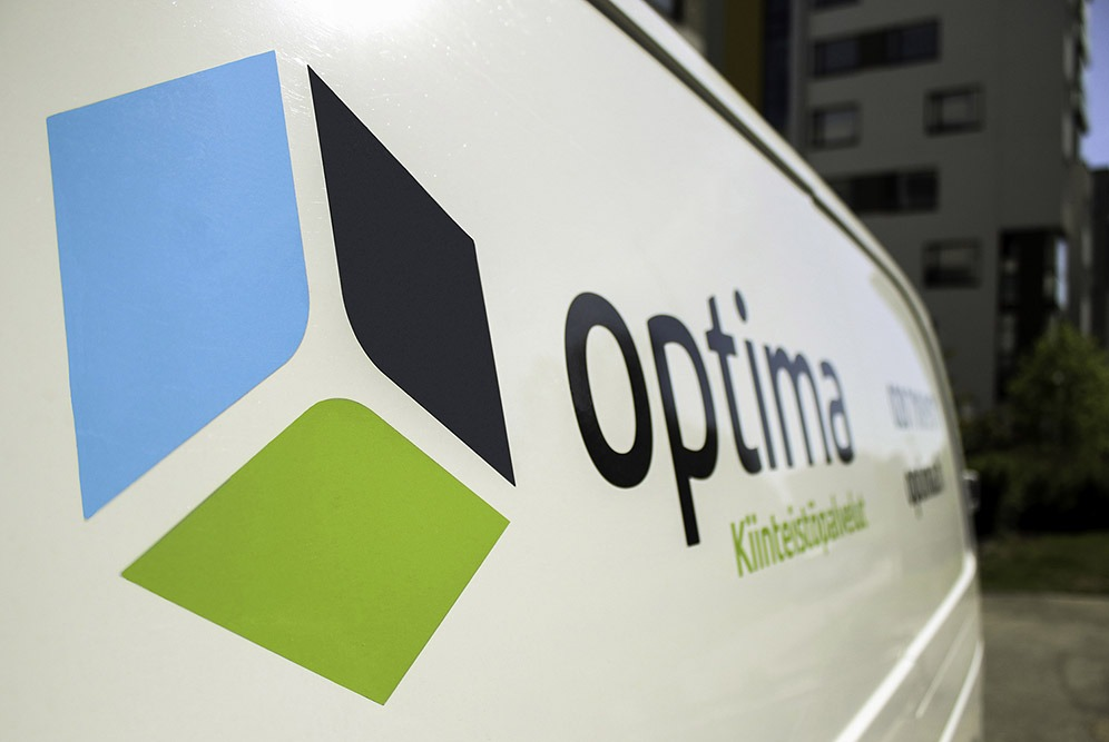 Kiinteistöhuoltoauton kylki, jossa Optima Kiinteistöpalveluiden logo