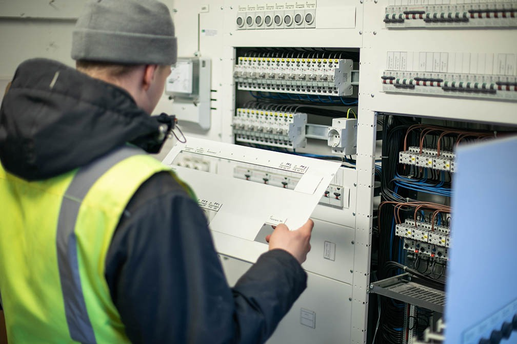 Optima Talotekniikka staff member working in the maintenance of electrical work