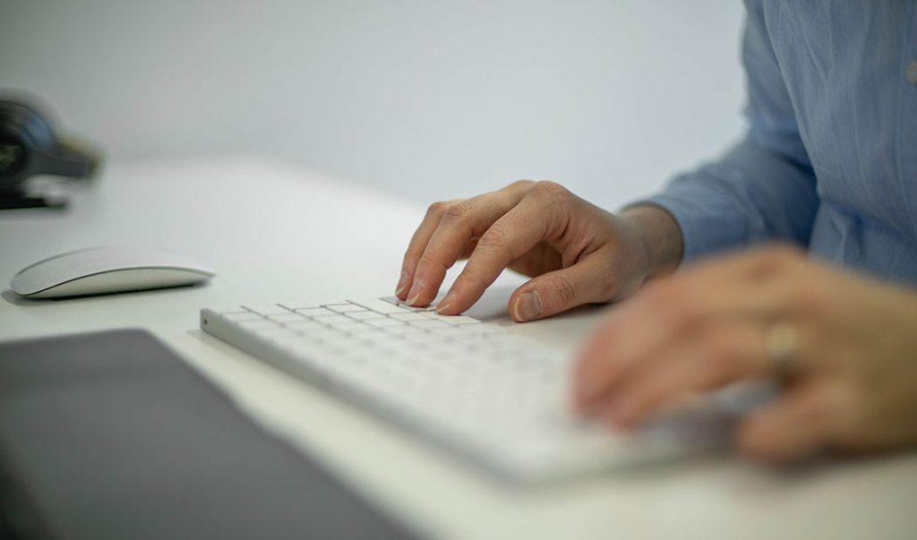 Henkilö työskentelee tietokoneella, kuvassa näppäimistöllä olevat kädet sekä hiiri.